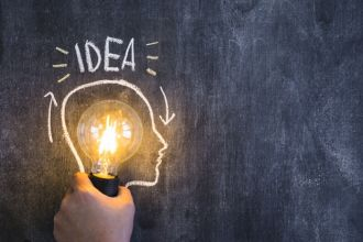 hand-holding-illuminated-light-bulb-with-outline-face-drawn-on-blackboard-with-idea-text_23-2147874059.jpg